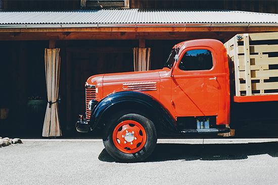 Rode vrachtwagen die geprakeerd staat.