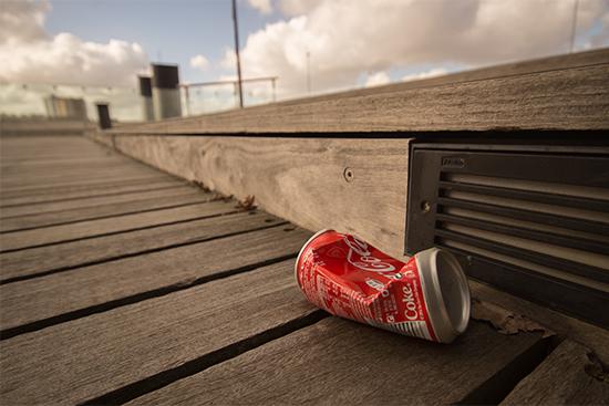 Een blikje cola op de grond nabij een zitbank.